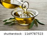 bottle of olive oil pouring in... | Shutterstock . vector #1169787523