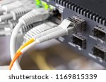 Stock photo close up of high speed fiber network switch and cables in datacenter 1169815339