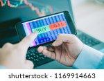 hand of trader holding mobile...   Shutterstock . vector #1169914663
