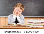 Tired elementary aged boy sitting at the desk with books - stock photo