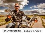 biker man wearing a leather... | Shutterstock . vector #1169947396