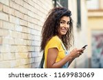 young arab woman texting with... | Shutterstock . vector #1169983069