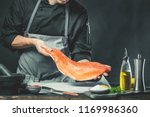 Stock photo the big salmon is in the hands of the chef cook he is using a knife to slice salmon fillet 1169986360