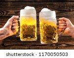 hands holding mugs of bavarian... | Shutterstock . vector #1170050503