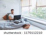 man working in bed on laptop... | Shutterstock . vector #1170112210