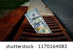Small photo of US 100 Dollar banknote down the street storm drain. Concept of senseless waste of money, loss, useless waste