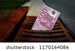Small photo of 500 Euro banknote down the street storm drain. Concept of senseless waste of money, loss, useless waste