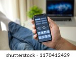 man on sofa holding phone with... | Shutterstock . vector #1170412429