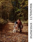 Stock photo young beautiful girl playing with a dog in the park autumn sunny day 1170465406