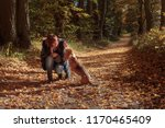 Stock photo young beautiful girl playing with a dog in the park autumn sunny day 1170465409