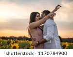 Small photo of Romantic Couple on a Love Moment in a Sunflower field