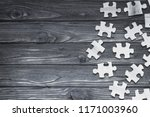 Small photo of Wooden puzzles scattered in a chaotic manner against the background of a wooden table. logics. disunity.