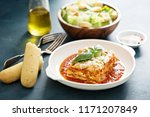 Traditional lasagna on white plate with caesar salad and breadsticks