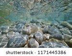 Pebbles And Rocks Below Water...