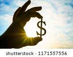 hand hold silhouette of dollar... | Shutterstock . vector #1171557556