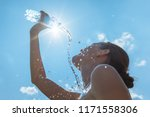 Small photo of Cooling off in the summer heat. Female runner splashing bottle of water on face.