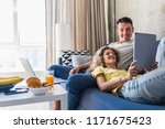 young couple sitting on sofa at ... | Shutterstock . vector #1171675423