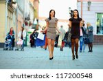 two elegant women walking the crowded city with shopping bags - stock photo