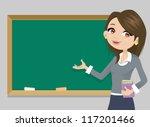 Teacher In Front Of  Chalkboar...