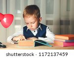 schoolboy is sitting at table... | Shutterstock . vector #1172137459