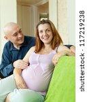 Happy pregnant couple on sofa in home interior - stock photo