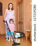 mother and daughter chores with vacuum cleaner in home - stock photo