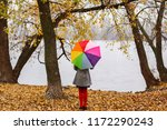 Small photo of Little girl with colorful rainbow umbrella staying in autumn park on yellow leaves looking at river at cloudy gloomy fall day. Lonliness and autumn melancholy.