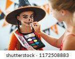 Small photo of happy family mother and daughter getting ready for halloween make make-up