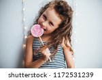 funny curly girl with lollypop... | Shutterstock . vector #1172531239