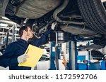 Auto car repair service center. Mechanic examining car - stock photo