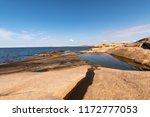 a calm blue ocean  red granite... | Shutterstock . vector #1172777053