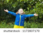 little girl playing in rainy... | Shutterstock . vector #1172837170