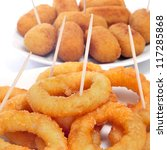 some plates with spanish calamares a la romana, squid rings breaded and fried, and croquettes served as tapas - stock photo
