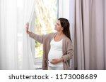 happy pregnant woman standing... | Shutterstock . vector #1173008689