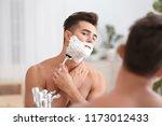 Young Man Shaving Near Mirror...