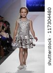 NEW YORK - OCTOBER 21: Girl walks runway for petite Parade show by Halabaloo during kids fashion week sponsored by Vogue Bambini & Swarovski Elements at Industria Superstudio on October 21 2012 in NYC - stock photo