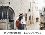 woman walking by tight streets... | Shutterstock . vector #1173097933