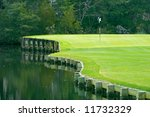 lovely golf green set among marsh and pond - stock photo