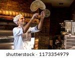 pizza chef tossing pizza dough... | Shutterstock . vector #1173354979