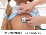 Little girl at the doctor - lung area examined with stethoscope - stock photo