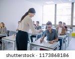 teacher giving an exam to high... | Shutterstock . vector #1173868186