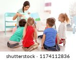 female teacher reading book to... | Shutterstock . vector #1174112836