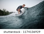 wakeboarder in swimsuit riding... | Shutterstock . vector #1174136929