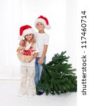 Kids wearing santa hats preparing to decorate the christmas tree - getting the props together - stock photo