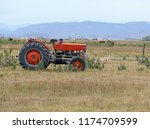 vintage red tractor on farm in... | Shutterstock . vector #1174709599