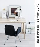 Comfortable chair standing near small table and nice frames pictures in stylish room.