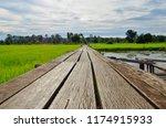 long old wooden bridge in green ... | Shutterstock . vector #1174915933