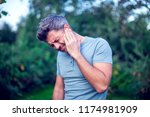 unhappy man having ear pain... | Shutterstock . vector #1174981909