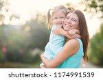 little girl hugging mother... | Shutterstock . vector #1174991539