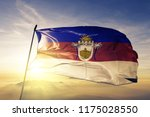 Small photo of Rocha department of Uruguay flag textile cloth fabric waving on the top sunrise mist fog